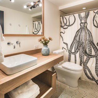 Trendy 3/4 gray floor bathroom photo in Other with open cabinets, medium tone wood cabinets, a two-piece toilet, white walls, a vessel sink, wood countertops and brown countertops