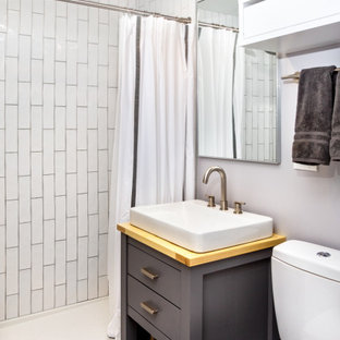 This is an example of a country 3/4 bathroom in Burlington with furniture-like cabinets, grey cabinets, an open shower, a one-piece toilet, white tile, subway tile, grey walls, porcelain floors, a vessel sink, wood benchtops, grey floor, a shower curtain, a single vanity and a freestanding vanity.