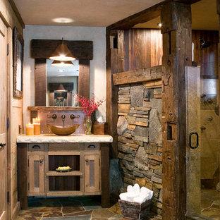 Modelo de cuarto de baño rural con lavabo sobreencimera, armarios estilo shaker, paredes beige, puertas de armario con efecto envejecido, baldosas y/o azulejos marrones y baldosas y/o azulejos de pizarra