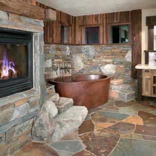 На фото: ванная комната в стиле рустика с настольной раковиной, фасадами с утопленной филенкой, фасадами цвета дерева среднего тона, отдельно стоящей ванной, бежевыми стенами и плиткой из сланца с