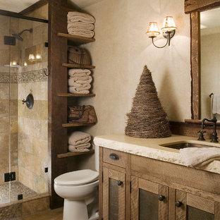 Cette image montre une douche en alcôve chalet avec un lavabo encastré, un placard à porte shaker, des portes de placard en bois brun, un WC séparé, un carrelage beige, un mur beige, un sol en galet, du carrelage en travertin et un plan de toilette blanc.