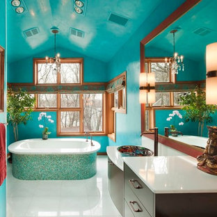 This is an example of a large contemporary master bathroom in Minneapolis with flat-panel cabinets, dark wood cabinets, blue tile, glass tile and onyx benchtops.