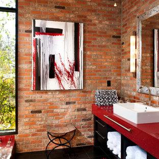 Cette photo montre une salle de bain tendance avec une vasque, un placard en trompe-l'oeil, des portes de placard noires et un plan de toilette rouge.