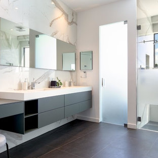 Example of a large trendy master multicolored tile and stone slab porcelain tile and gray floor bathroom design in Miami with flat-panel cabinets, gray cabinets, white walls, an integrated sink, a hinged shower door and white countertops