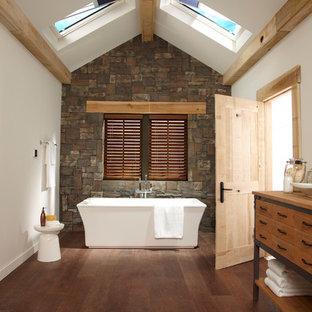 Ejemplo de cuarto de baño contemporáneo con armarios tipo mueble, puertas de armario de madera oscura, bañera exenta, baldosas y/o azulejos grises, paredes blancas, suelo de madera en tonos medios, lavabo sobreencimera, encimera de madera, suelo marrón y encimeras marrones