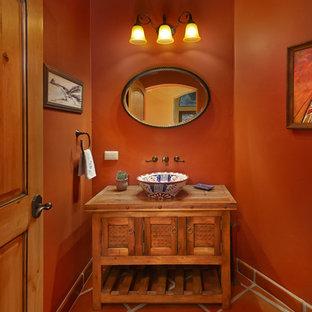 フェニックスの巨大なサンタフェスタイルのおしゃれなバスルーム (浴槽なし) (家具調キャビネット、淡色木目調キャビネット、一体型トイレ、テラコッタタイル、茶色い壁、テラコッタタイルの床、ベッセル式洗面器、木製洗面台) の写真