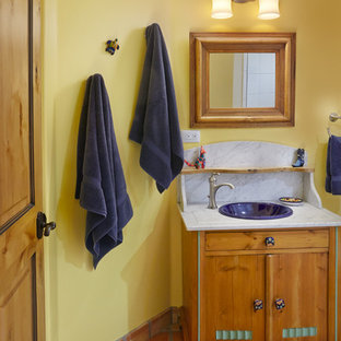 Esempio di un'ampia stanza da bagno american style con consolle stile comò, ante in legno chiaro, doccia a filo pavimento, WC monopezzo, piastrelle in terracotta, pareti beige, pavimento in terracotta, lavabo da incasso, piastrelle grigie e top in granito