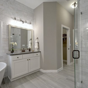 Example of a transitional master gray tile painted wood floor and gray floor bathroom design in Jacksonville with shaker cabinets, white cabinets, gray walls, an undermount sink, a hinged shower door and gray countertops