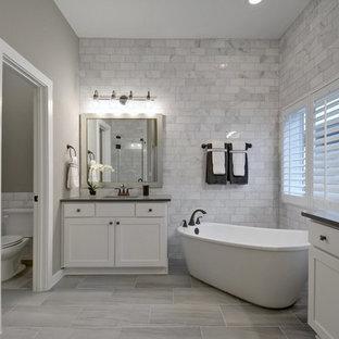 Ispirazione per una stanza da bagno padronale classica con ante in stile shaker, ante bianche, vasca freestanding, doccia alcova, WC a due pezzi, piastrelle grigie, piastrelle bianche, pareti grigie, lavabo sottopiano, pavimento grigio, porta doccia a battente e top nero