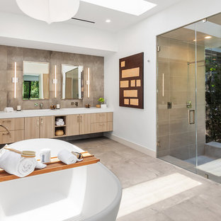 Inspiration for a contemporary master beige tile gray floor alcove shower remodel in Los Angeles with flat-panel cabinets, light wood cabinets, white walls, a hinged shower door and white countertops