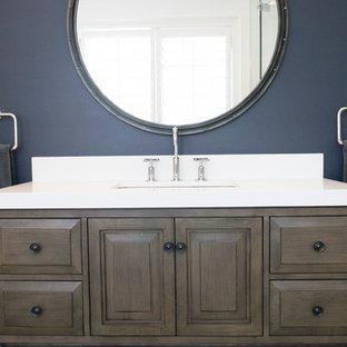 Modelo de cuarto de baño de tamaño medio con lavabo bajoencimera, armarios tipo mueble, puertas de armario de madera oscura, encimera de cuarzo compacto, ducha esquinera, sanitario de una pieza, baldosas y/o azulejos blancos, baldosas y/o azulejos de cerámica, paredes azules y suelo de baldosas de porcelana