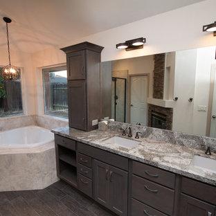 Esempio di una grande stanza da bagno padronale industriale con lavabo sottopiano, ante in stile shaker, ante grigie, top in quarzo composito, vasca ad angolo, WC a due pezzi, piastrelle grigie, piastrelle in gres porcellanato, pareti grigie e pavimento in gres porcellanato