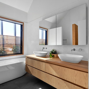 This is an example of a contemporary master bathroom in Melbourne with marble benchtops.