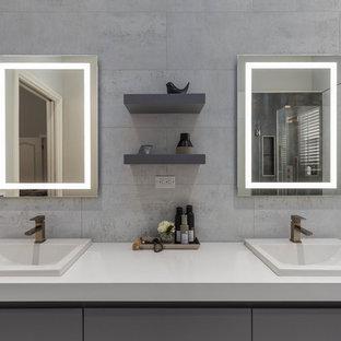 Foto de cuarto de baño principal, minimalista, grande, con armarios con paneles lisos, puertas de armario grises, bañera encastrada sin remate, ducha esquinera, sanitario de una pieza, baldosas y/o azulejos grises, baldosas y/o azulejos de porcelana, paredes grises, suelo de baldosas de porcelana, lavabo bajoencimera, encimera de granito, suelo blanco, ducha con puerta con bisagras y encimeras blancas