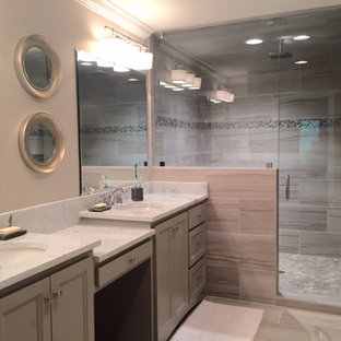 Bathroom - mid-sized transitional master gray tile and ceramic tile ceramic floor and gray floor bathroom idea in Birmingham with an undermount sink, recessed-panel cabinets, gray cabinets, marble countertops, gray walls and a hinged shower door