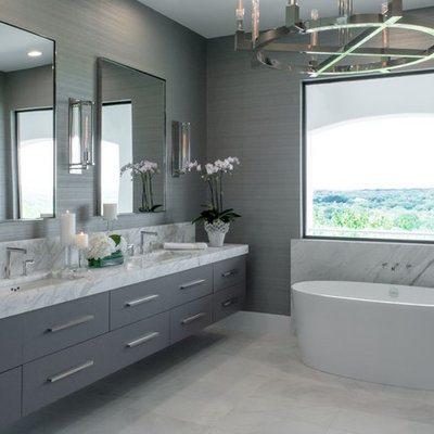Inspiration for a contemporary gray tile gray floor freestanding bathtub remodel in Austin with flat-panel cabinets, gray cabinets, gray walls and an undermount sink