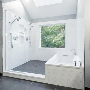 ニューヨークの広いモダンスタイルのおしゃれなマスターバスルーム (家具調キャビネット、分離型トイレ、グレーの壁、セラミックタイルの床、ヴィンテージ仕上げキャビネット、アルコーブ型浴槽、洗い場付きシャワー、白いタイル、サブウェイタイル、ベッセル式洗面器、人工大理石カウンター、グレーの床、オープンシャワー) の写真