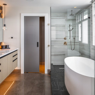 This is an example of a mid-sized contemporary master bathroom in Vancouver with flat-panel cabinets, light wood cabinets, a freestanding tub, a corner shower, multi-coloured tile, white walls, concrete floors, an undermount sink, quartzite benchtops, grey floor, an open shower and turquoise benchtops.