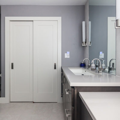 Example of a large transitional master gray tile and cement tile ceramic tile corner shower design in New York with flat-panel cabinets, dark wood cabinets, a two-piece toilet, blue walls, a trough sink and quartz countertops