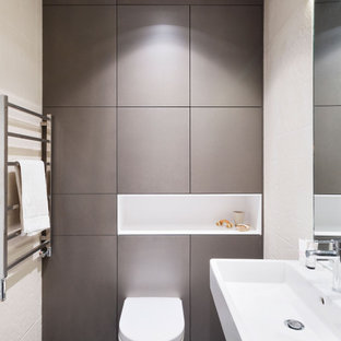 Medium sized contemporary shower room bathroom in London with open cabinets, a wall mounted toilet, beige walls, porcelain flooring, an integrated sink, black floors and white worktops.