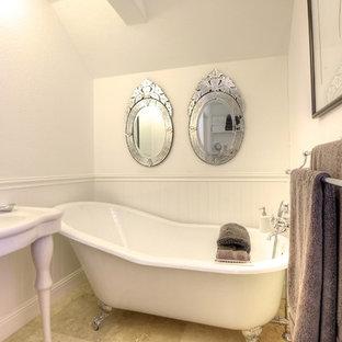 Ispirazione per una piccola stanza da bagno per bambini vittoriana con ante in stile shaker, ante bianche, vasca freestanding, WC sospeso, piastrelle beige, piastrelle in pietra, pareti bianche, pavimento in pietra calcarea e lavabo a consolle