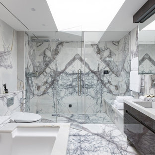 This is an example of a contemporary ensuite bathroom in London with flat-panel cabinets, brown cabinets, a submerged bath, an alcove shower, a wall mounted toilet, marble tiles, white walls, marble flooring, an integrated sink, white floors and a hinged door.