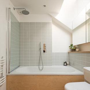На фото: главная ванная комната среднего размера в скандинавском стиле с накладной ванной, раздельным унитазом, белыми стенами, душем над ванной, серой плиткой и пробковым полом с
