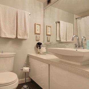 Неиссякаемый источник вдохновения для домашнего уюта: маленькая главная ванная комната в современном стиле с фасадами островного типа, белыми фасадами, ванной в нише, душем над ванной, унитазом-моноблоком, зеленой плиткой, стеклянной плиткой, зелеными стенами, полом из керамогранита, настольной раковиной, столешницей из ламината, серым полом и шторкой для душа