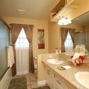 ボイシの小さいトラディショナルスタイルのおしゃれなバスルーム (浴槽なし) (オーバーカウンターシンク、フラットパネル扉のキャビネット、ベージュのキャビネット、ラミネートカウンター、アルコーブ型浴槽、シャワー付き浴槽、分離型トイレ、ベージュの壁、リノリウムの床) の写真