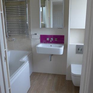Ispirazione per una piccola stanza da bagno per bambini minimal con lavabo sospeso, ante lisce, ante grigie, vasca da incasso, vasca/doccia, WC sospeso, piastrelle rosa, pareti beige e pavimento in linoleum