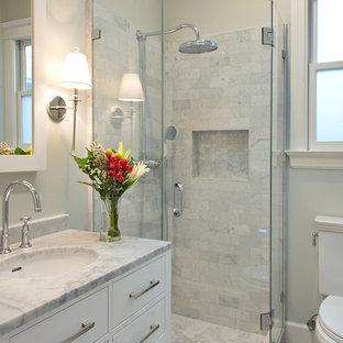 Mittelgroßes Klassisches Duschbad mit flächenbündigen Schrankfronten, weißen Schränken, Eckdusche, Toilette mit Aufsatzspülkasten, grauen Fliesen, Porzellanfliesen, grauer Wandfarbe, Porzellan-Bodenfliesen, Einbauwaschbecken, Marmor-Waschbecken/Waschtisch, grauem Boden und Falttür-Duschabtrennung in Chicago