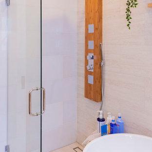Imagen de cuarto de baño principal, contemporáneo, de tamaño medio, con armarios tipo mueble, puertas de armario de madera clara, bañera exenta, ducha esquinera, sanitario de una pieza, baldosas y/o azulejos beige, baldosas y/o azulejos de porcelana, paredes beige, suelo laminado, lavabo bajoencimera, encimera de madera, suelo beige, ducha abierta y encimeras marrones