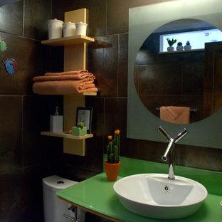 Ispirazione per una piccola stanza da bagno boho chic con ante di vetro, ante verdi, doccia a filo pavimento, WC monopezzo, piastrelle marroni, piastrelle di cemento, pavimento con piastrelle in ceramica, top in vetro, pareti marroni, lavabo a bacinella, pavimento beige e doccia aperta