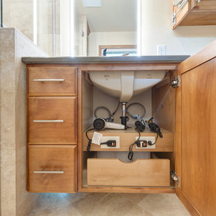 ポートランドの小さいトラディショナルスタイルのおしゃれなマスターバスルーム (レイズドパネル扉のキャビネット、中間色木目調キャビネット、バリアフリー、壁掛け式トイレ、ベージュのタイル、トラバーチンタイル、ベージュの壁、トラバーチンの床、アンダーカウンター洗面器、クオーツストーンの洗面台、マルチカラーの床、開き戸のシャワー) の写真