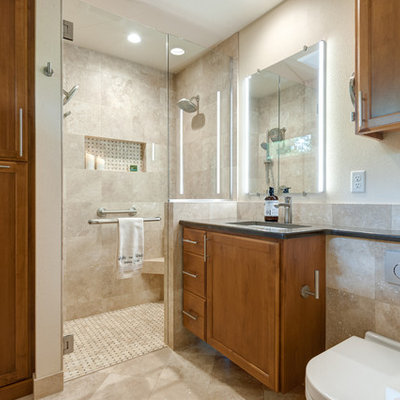 Small elegant master beige tile and travertine tile travertine floor and multicolored floor walk-in shower photo in Portland with raised-panel cabinets, medium tone wood cabinets, a wall-mount toilet, beige walls, an undermount sink, quartz countertops and a hinged shower door