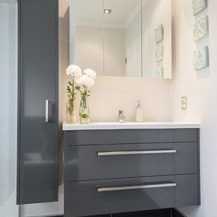 Idee per una piccola stanza da bagno padronale contemporanea con ante lisce, ante grigie, top in superficie solida, doccia ad angolo, pareti grigie, pavimento con piastrelle in ceramica e lavabo sospeso