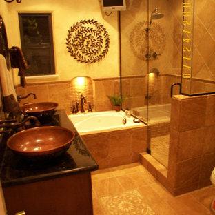 ロサンゼルスの地中海スタイルのおしゃれな浴室 (家具調キャビネット、濃色木目調キャビネット、大型浴槽、一体型トイレ、トラバーチンの床、ベッセル式洗面器、御影石の洗面台) の写真