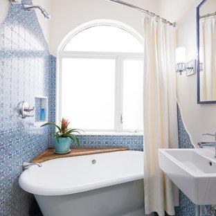 На фото: маленькая главная ванная комната в средиземноморском стиле с отдельно стоящей ванной, душем над ванной, керамической плиткой, белыми стенами, полом из мозаичной плитки, подвесной раковиной, шторкой для душа, белой столешницей, синей плиткой и бирюзовым полом с