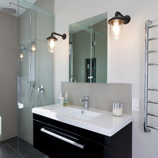 Пример оригинального дизайна: маленькая главная ванная комната в современном стиле с монолитной раковиной, плоскими фасадами, черными фасадами, столешницей из ламината, унитазом-моноблоком, серой плиткой, керамогранитной плиткой, серыми стенами и полом из керамогранита