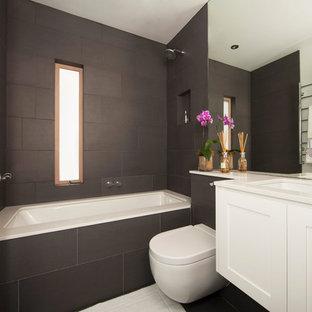 Diseño de cuarto de baño actual, de tamaño medio, con lavabo bajoencimera, armarios con paneles empotrados, puertas de armario blancas, bañera encastrada sin remate, combinación de ducha y bañera, sanitario de pared, baldosas y/o azulejos negros, paredes blancas, suelo de baldosas de porcelana, baldosas y/o azulejos de cerámica y ducha abierta