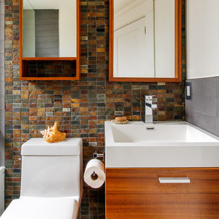 Inspiration for a small contemporary kids' slate tile bathroom remodel in Toronto with an integrated sink, flat-panel cabinets, medium tone wood cabinets, solid surface countertops and a one-piece toilet