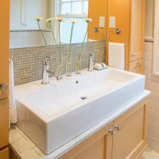 Diseño de cuarto de baño tradicional renovado, pequeño, con puertas de armario naranjas, lavabo de seno grande, armarios estilo shaker, encimera de mármol, bañera empotrada, sanitario de dos piezas, baldosas y/o azulejos multicolor, paredes verdes y suelo de baldosas de cerámica
