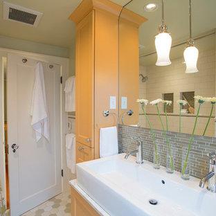 Modelo de cuarto de baño tradicional, pequeño, con lavabo de seno grande, combinación de ducha y bañera, armarios con paneles empotrados, baldosas y/o azulejos verdes, baldosas y/o azulejos de vidrio, encimera de mármol, paredes verdes, suelo de baldosas de cerámica y puertas de armario amarillas