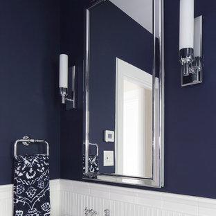 Diseño de cuarto de baño tradicional, de tamaño medio, con lavabo integrado, puertas de armario blancas, bañera empotrada, combinación de ducha y bañera, baldosas y/o azulejos blancos, paredes azules, armarios tipo mueble, sanitario de una pieza y baldosas y/o azulejos de cerámica