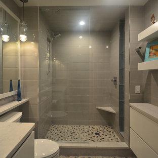 Exempel på ett litet modernt vit vitt en-suite badrum, med släta luckor, vita skåp, en dusch i en alkov, en toalettstol med separat cisternkåpa, grå kakel, porslinskakel, grå väggar, klinkergolv i småsten, ett undermonterad handfat, granitbänkskiva, flerfärgat golv och med dusch som är öppen