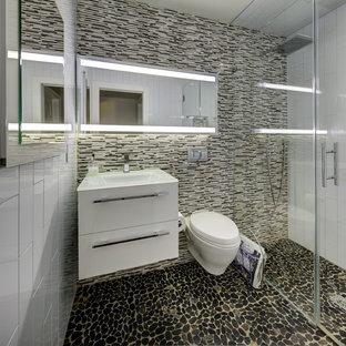 Esempio di una piccola stanza da bagno padronale moderna con ante lisce, ante bianche, doccia a filo pavimento, WC sospeso, pistrelle in bianco e nero, piastrelle a listelli, pareti bianche, pavimento con piastrelle di ciottoli, top in vetro e lavabo integrato