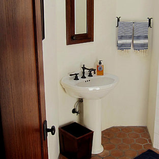 Design ideas for a small mediterranean master bathroom in Santa Barbara with a corner shower, a two-piece toilet, terra-cotta tile, white walls, terra-cotta floors, a pedestal sink, open cabinets, medium wood cabinets, white tile, red floor and white benchtops.