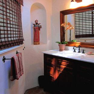 Идея дизайна: ванная комната среднего размера в средиземноморском стиле с фасадами островного типа, темными деревянными фасадами, душем над ванной, белыми стенами, полом из терракотовой плитки, душевой кабиной, врезной раковиной, мраморной столешницей, красным полом, шторкой для ванной и белой столешницей