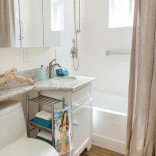 Imagen de cuarto de baño infantil, costero, pequeño, con lavabo bajoencimera, armarios estilo shaker, puertas de armario blancas, encimera de granito, bañera empotrada, combinación de ducha y bañera, sanitario de una pieza, baldosas y/o azulejos grises, suelo vinílico, paredes blancas y encimeras amarillas