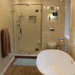 Inredning av ett modernt stort beige beige en-suite badrum, med släta luckor, vita skåp, ett fristående badkar, en dusch i en alkov, en vägghängd toalettstol, vit kakel, porslinskakel, beige väggar, laminatgolv, ett undermonterad handfat, bänkskiva i kvartsit, brunt golv och dusch med gångjärnsdörr